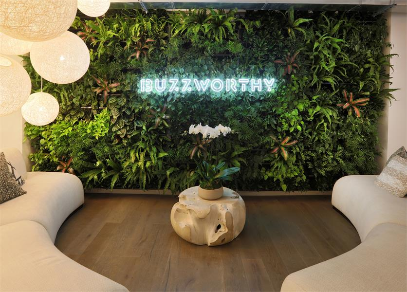 This luxurious living wall greets visitors upon entrance to the office space, nestled behind neon lettering to create a strong