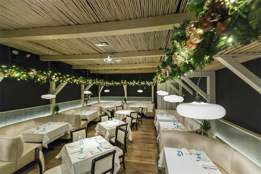 Lights twinkle through the evergreen frame of this restaurant which radiates through the space.