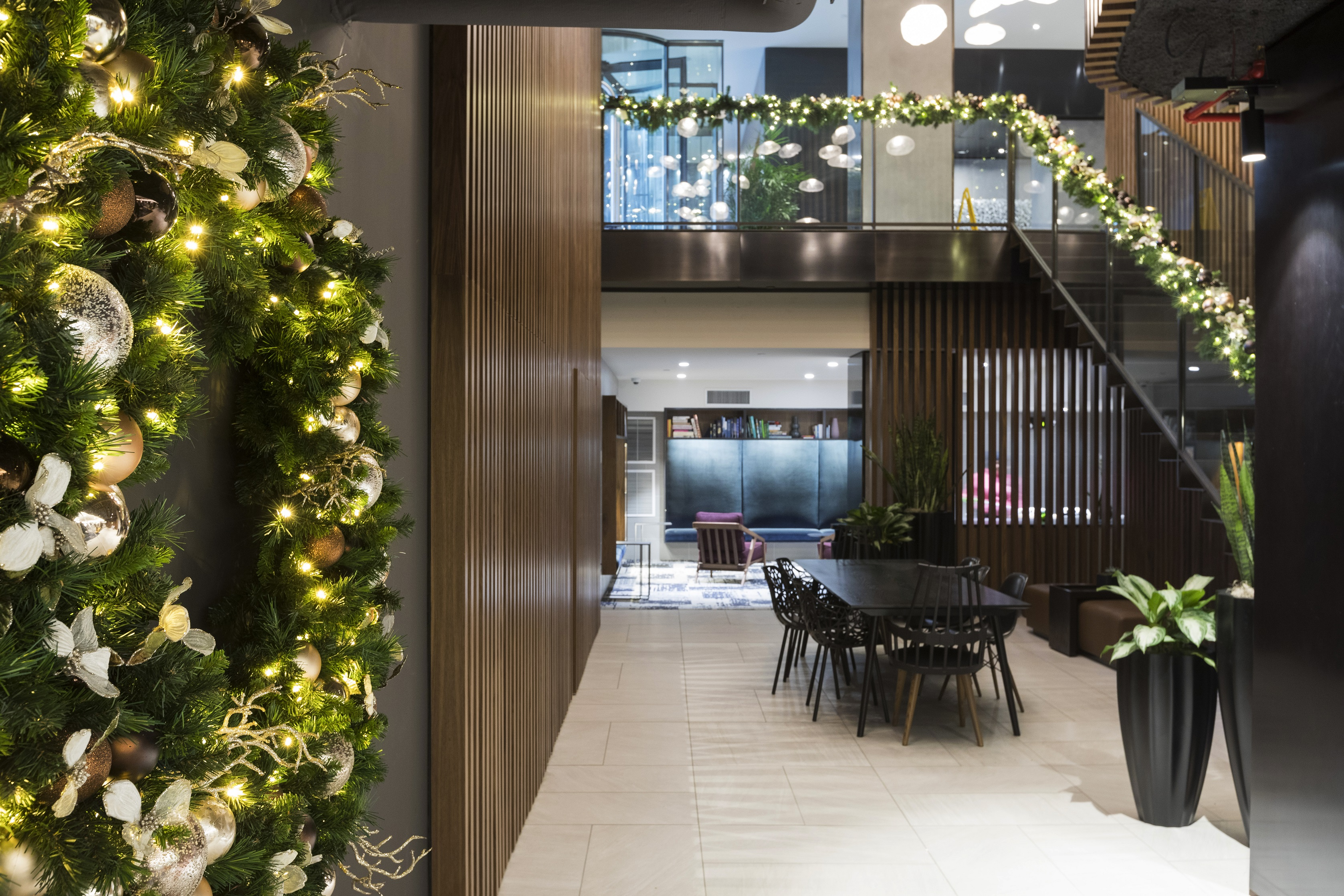 The warm wooden tones of this modern Manhattan lobby are echoed through naturalistic holiday elements.
